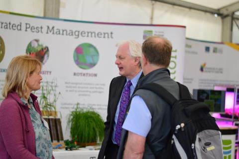 IPM@Hutton members talking about IPM research at the James Hutton Institute with a member fo the public and the 2019 Royal Highland Show